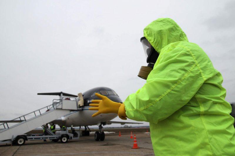 Работник аэропорта в защитном костюме