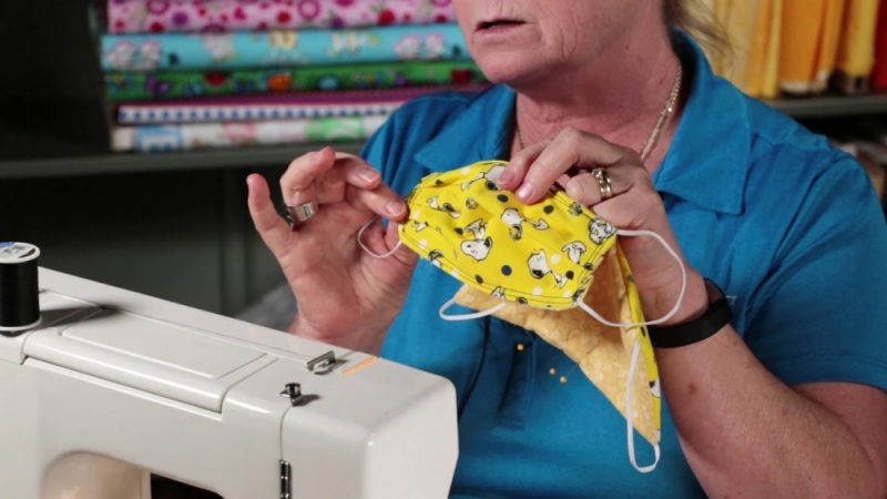Женщина делает медицинскую маску своими руками